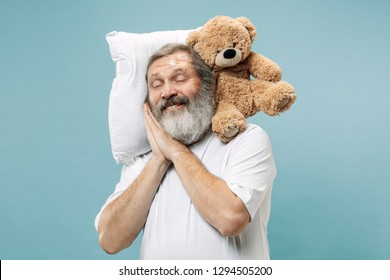 Tired surprised happy man sleeping at home or office having too much work. Bored businessman with pillow and toy bear. The busy, boring, worried, be late, concerned, sleep day, introuble concept