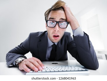Tired or surprised young businessman in black suit, working with computer at office. Success in business concept.