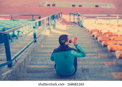 tired sweaty athlete drinking water at the stadium on the stairs (intentional vintage color)