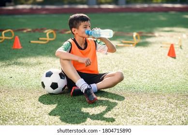 Müde Teenager in Fußball-Uniform Getränke mit Wasser aus Plastikflasche nach intensivem Training im Stadion am Morgen.