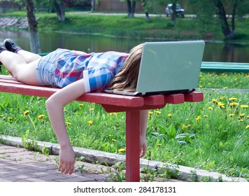 tired teen girl is a summer day on the bench, his face buried in a notebook