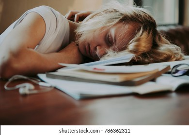 A tired teenage girl sleeping on her table while doing her school homework. Laziness and procrastination concept. Toned image