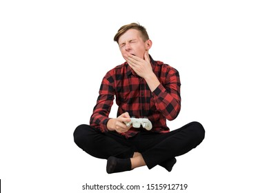 Tired teenage guy seated on the floor playing video games isolated over white background. Sleepy boy yawning as holding joystick console, addicted virtual world.