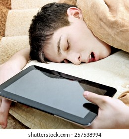 Tired Teenager sleep on the Bed with Tablet Computer