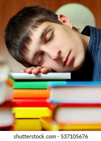 Tired Teenager sleep on the Books at the Home