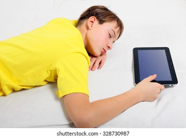 Tired Teenager sleep with the Tablet Computer on the Bed