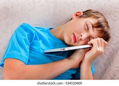 Tired Teenager sleep with Tablet Computer on the Sofa