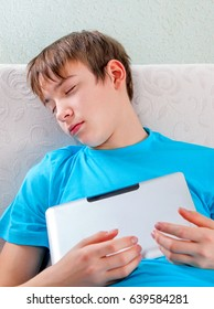 Tired Teenager sleep with Tablet Computer at the Home