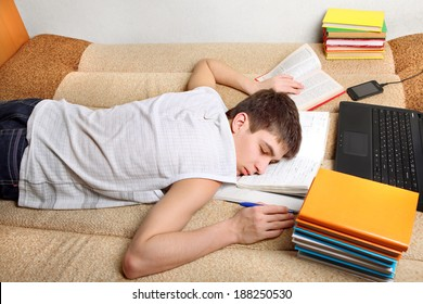 Tired Teenager sleeping with the Books and Laptop on the Sofa at the Home