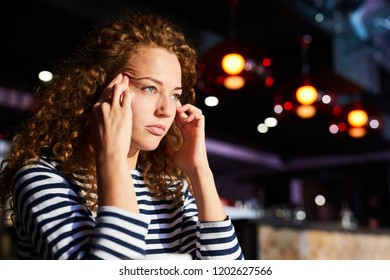 Tired or tense woman with wavy hair touching her temples while trying to concentrate