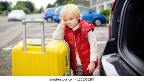 Tired toddler boy ready for going to road trip with his parents. Automobile trip in the countryside. Roadtrip for family with little kids