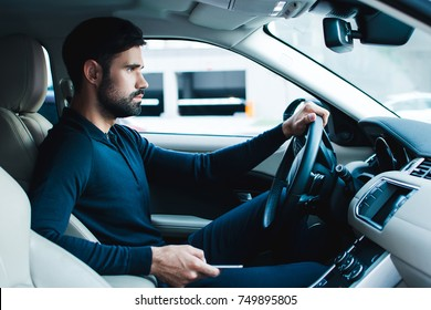 Tired of traffic jam. Side view of handsome young man holding his smart phone while sitting in car