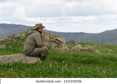tired traveler in the mountains - a man in a hat and travel clothes sits on a stone in a deserted mountain landscape, looking into the distance