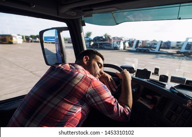 Tired truck driver sleeping in his cabin. Caucasian driver falling asleep on steering wheel. Working overtime.