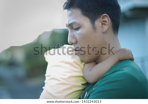 Tired unhappy father holding his baby. Postpartum depression.