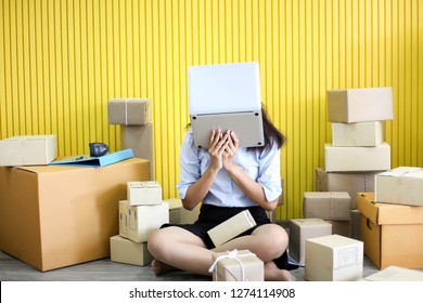 Tired unhappy of   Young asian girl is freelancer Start up small business owner writing address on cardboard box at workplace,Shipping shopping online small business entrepreneur SME or freelance