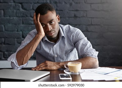 Tired and unhappy young manager with headache having exhausted and overworked look, leaning on his elbow on desk while working through papers late at night, drinking another cup of coffee