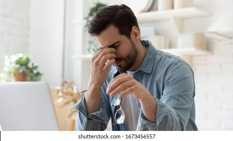 Tired unhealthy man taking of glasses, massaging nose bridge, feeling unwell, suffering from eye strain after long laptop use, exhausted young male student, freelancer relieving dry eyes syndrome