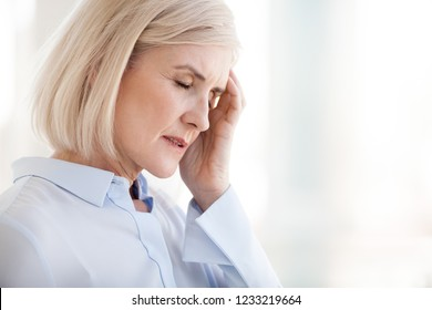 Tired upset mature old businesswoman suffering from strong chronic headache migraine or memory loss at work, stressed dizzy fatigued middle aged senior woman office worker feels pain in aching head