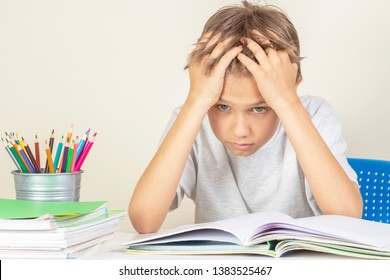 Tired upset schoolboy with pile of school books and notebooks