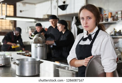 Tired and upset waitress in kitchen of restaurant
