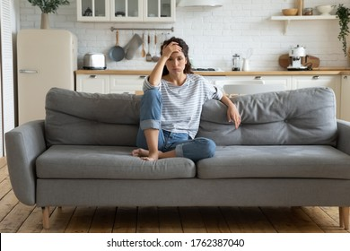 Tired upset woman worried about tiredness from domestic work sitting at couch. Frustrating mom stressful feels heaviness and headache at home. Fatigue parent trying relaxing in living room. - Shutterstock ID 1762387040