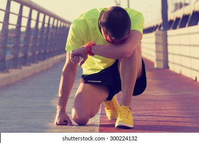 Tired urban jogger making a pause after forcing his body on a big bridge.