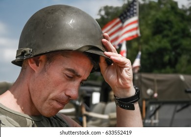Tired Vietnam War era soldier puts oh his helmet, with American flag in background
