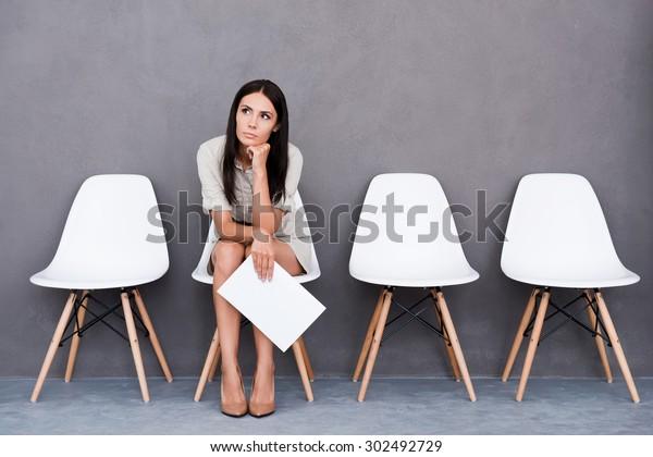 Müde des Wartens. gelangte junge Geschäftsfrau, die Papier hält und auf einem Stuhl auf grauem Hintergrund sitzend wegguckt
