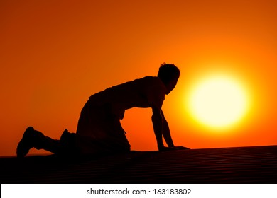 Tired and weaken man on all fours with gold sunset sun disk on background