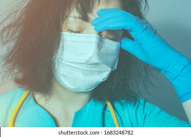 Tired and weary nurse in medical uniform puts her hand to her forehead. Due to lack of staff, doctors are working without rest due to a coronavirus infection