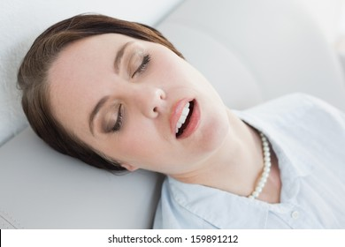 Tired well dressed young woman sitting and sleeping on sofa at home