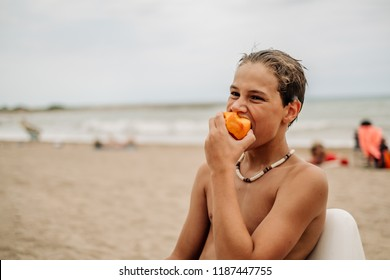 Tired wet boy sitting and eating peach on the beach