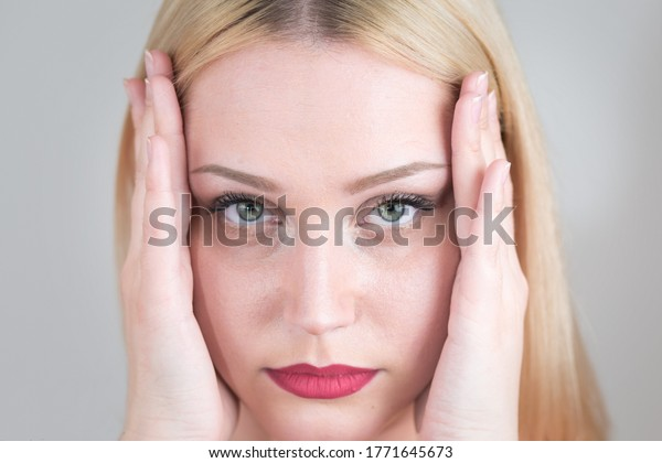 Tired white woman with headache keeps her head from problems with her hands. Close-up