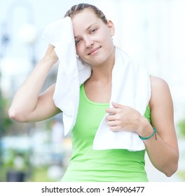 Tired woman after fitness time and exercising in city street park at beautiful summer morning. Sport fitness model caucasian ethnicity training outdoor.