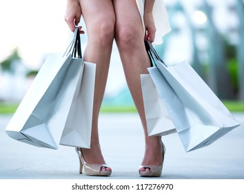Tired woman after a shopping spree holding bags