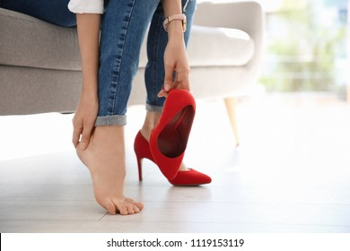 Tired woman with beautiful legs taking off shoes at home, closeup