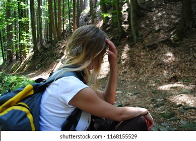 Tired woman with blonde hair on a trail sitting and relaxing touching sweaty head and waiting for recovery. Backpack on backs while hiking to the mountains in the forest.