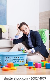 Tired woman cleaning up room from kids toys