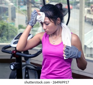 Tired woman drying his sweaty forehead with a towel in the gym. Sporting woman wiped the sweat from his brow in the gym. Fatigue in the gym. Training woman in the gym wiping sweat towel.