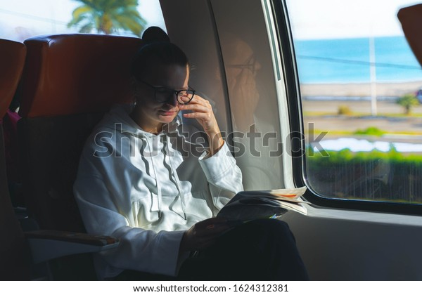 tired woman in eyeglasses rubbing eyes and sitting in train near big window and holding newspaper. woman with closed eyes. sea and palms outside train window.