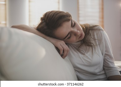 Tired woman falling asleep on the couch in the living room