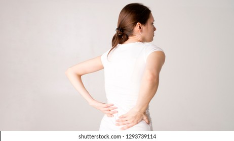 Tired woman feeling neck pain, massaging tense muscles. back pain and lower back view