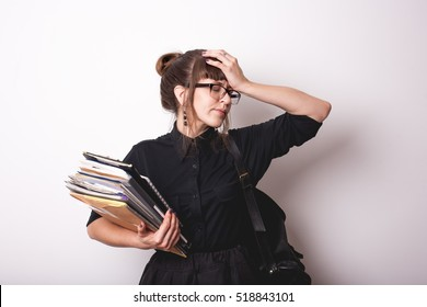 Tired woman holding documents and folders with hand on face. Isolated on white