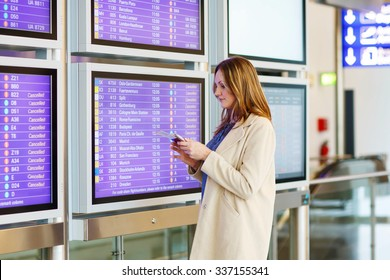 Tired woman at international airport with tickets and passport checking mobile for flight. Annoyed passenger waiting. Canceled flight due to pilot strike.