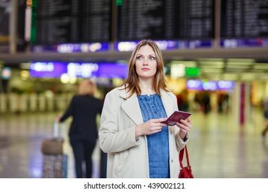 Tired woman at international airport walking through terminal. Upset female tourist passenger waiting. Canceled flight due to pilot strike.