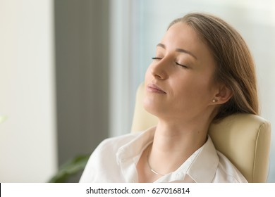 Tired woman lying on back chair with closed eyes. Businesswoman doing deep relaxation exercises during hard working day. Beautiful girl dreaming about future in office. Short meditation at workplace