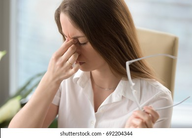 Tired woman massaging nose bridge while holding glasses, feeling eye strain, exhausted lady suffering from headache or migraine, discomfort after long wearing spectacles, eyesight problem, head shot