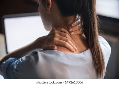 Tired woman massaging rubbing stiff sore neck tensed muscles fatigued from computer work in incorrect posture feeling hurt joint shoulder back pain ache, fibromyalgia concept, close up rear view