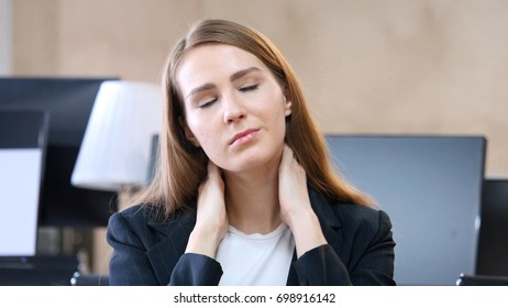 Tired Woman in Office with Neck Pain